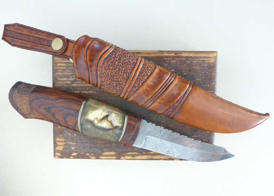 Blade in Damasteel grinded by Robert Mattsson, handle in dessert iron wood, musk ox antler and brass spacers. sheath in raw hide leather.