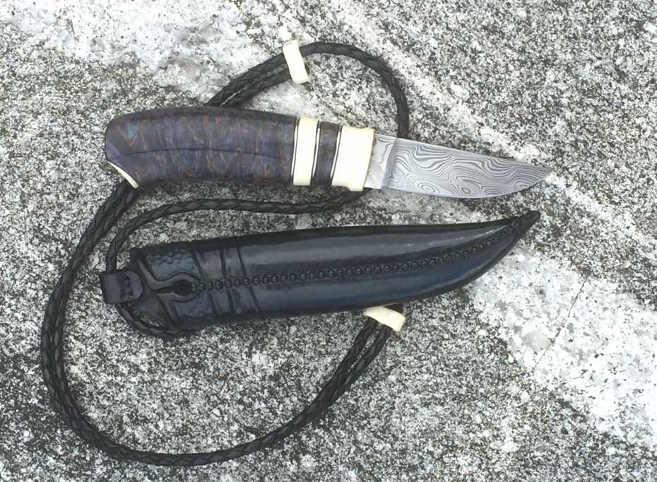 blade in Damasteel, handle in mamuth, cross cut masur birch an pewter spacers. Sheath in raw hide leather.