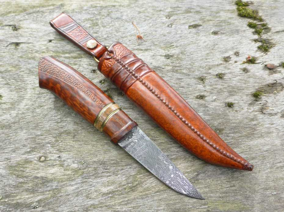 Damascus forged by Doug Ponzio, grinded by Anders Hedlund. Handle in Iron wood, mammoth, Snake wood and brass spacers. Sheath in raw hide leather.